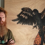 LOYALTY and COURAGE Spirit Bird Diptych artist Darren Trebilco standing with 'COURAGE'