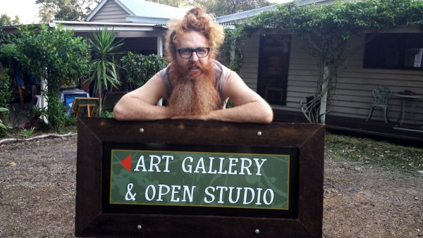 Darren Trebilco leaning on the new sign to the entrance of the Solitude Art Gallery and Open Studio